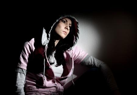 Young white girl sitting looking sad wearing pink sweatshirt with hood