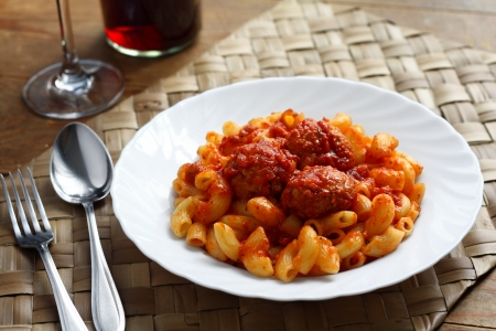 Bend tubes pasta with tomato sauce and meat balls on white plate