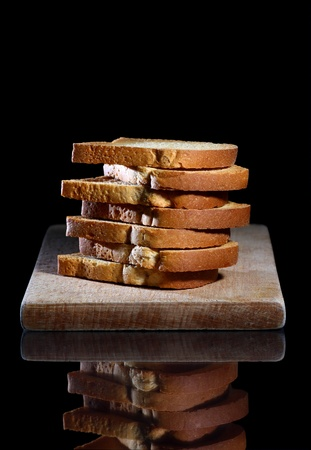 Close up of toasted white bread in slices on cutting board over black background