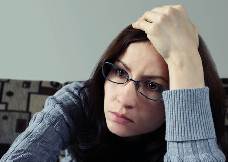 Close up of a young worried brunette wearing glasses