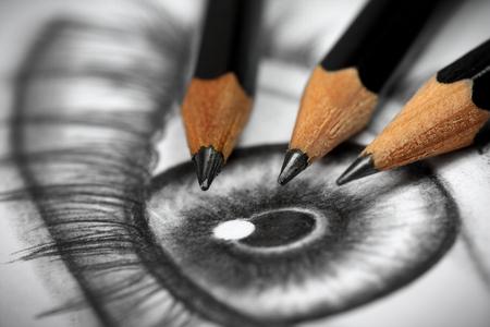 grafite: Feche acima de um desenho de olho e três lápis grafite Imagens