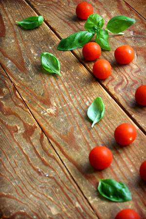 Fresh leaves of basil placed with cherry tomatoes on wooden