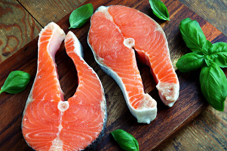 Two pieces of red salmon fillets placed on the wooden cutting board Stock Photo