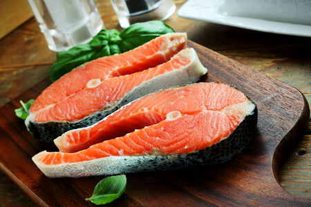 Two pieces of red salmon fillets placed on the wooden cutting board Stock Photo - 28966112