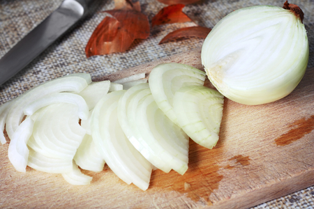 Close up view of sliced onion on wooden cutting board