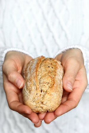 Close up of female hands holding whole grain roll