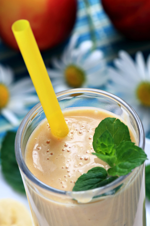 Glass of fresh banana peach smoothie close up