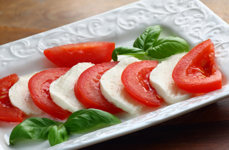 Close up of sliced mozzarella cheese and fresh red tomatoes