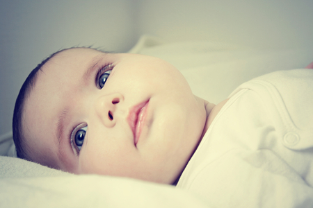 Close up of pretty infant face looking happy Stock Photo