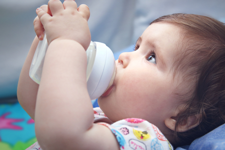 nine  months: Nine months old baby drinking milk from bottle holding with both hands Stock Photo