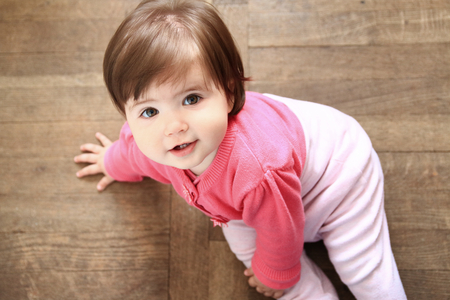 Happy 11 month girl looking up from the wooden floor