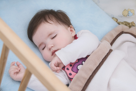 Close up on the face of sleeping child in her cot Stock Photo