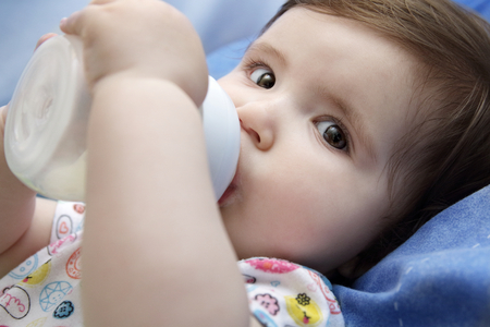 Nine months old baby drinking milk from bottle holding with both hands Stock Photo