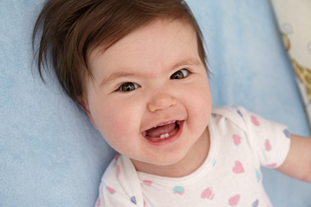 first teeth: Excited baby girl smiling widely to show her first teeth Stock Photo