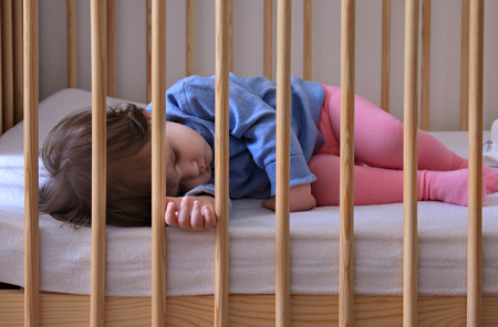 Baby girl dreaming during the day in her cot Stock Photo