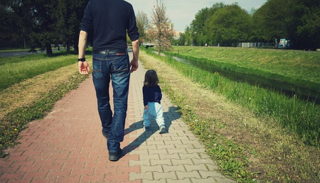 Child is walking with daddy on a sunny day Stock Photo