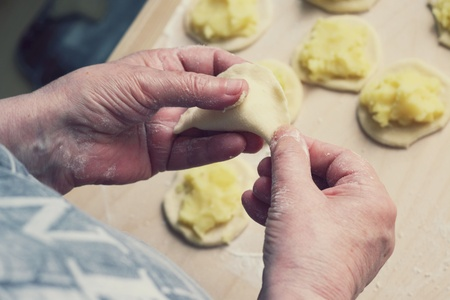 Close up of female hands making Polish dumplings