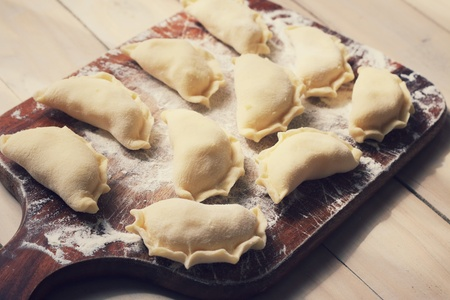 Polish dumplings arranged on wooden cutting board Stock Photo