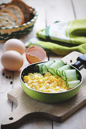 Scrambled eggs with cucumber in pan