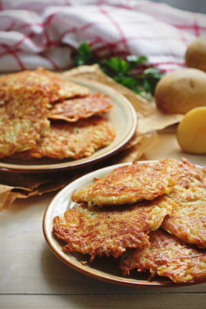 Two plates of crispy hash browns prepared at home on a wooden background Stock Photo
