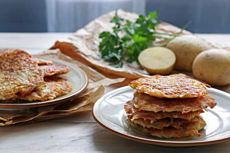 Plate of crispy homemade potato hash browns on wooden table