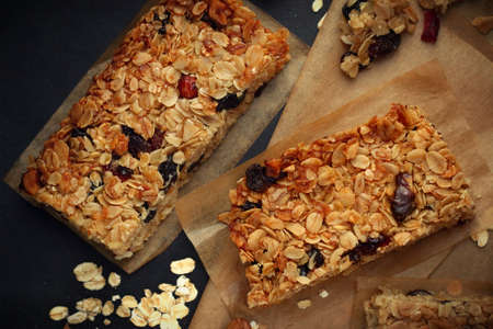 Home baked granola bars with nuts and cranberries over black background top view