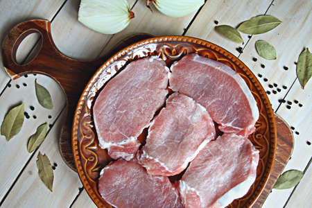 Pork raw steaks on a brown plate over wooden background top view Stock Photo