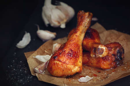 Roasted chicken drumsticks with garlic on black background close up Stock Photo