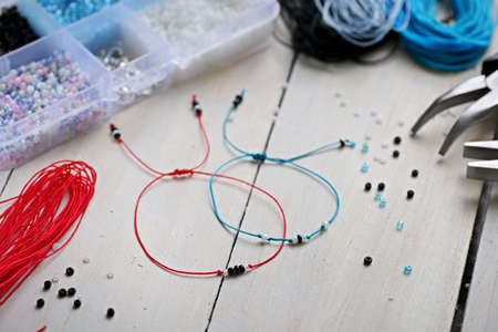 Handmade blue and red nylon cord bracelets with small beads over wooden background Stock Photo