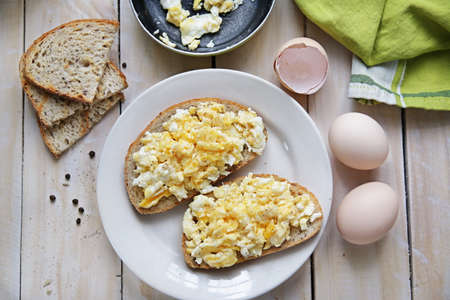 Top view of quick breakfast made of scrambled eggs served on wooden table Stock Photo