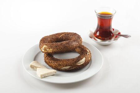 two simit that is circular bread on white dish with cheese and tea