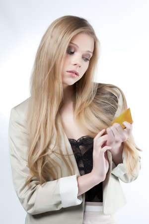 blond woman holding a golden credit card on a white background photo