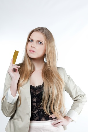 Happy young woman holding a golden credit card on a white background photo