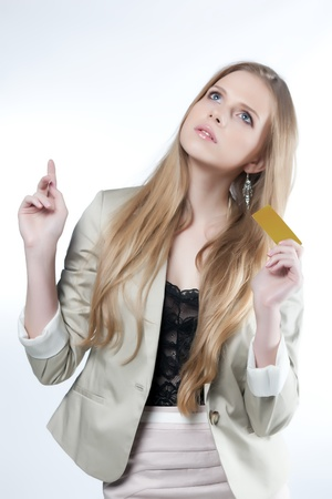 Happy young woman with golden credit card on a white background photo