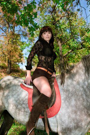 femme a cheval: jeune fille en bottes posant sur un cheval sur un fond de vert