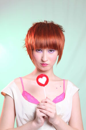 Girl with candy heart with red hair in white dress photo