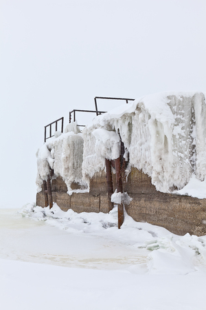 snowbanks: winter berth at the quay of the river covered with ice and snow Stock Photo