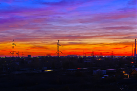 industry moody: Colorful sunset in the industrial suburb with pipes and high-voltage tower