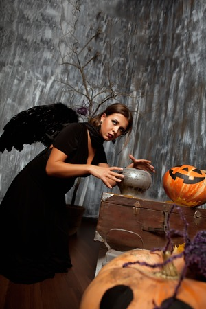 devil cartoon: Black Witch brews a potion with wings surrounded by halloween pumpkin Stock Photo