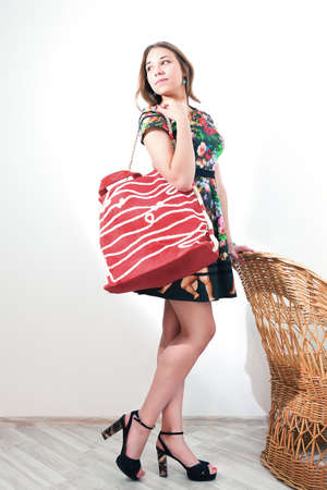 spender: girl posing while standing near  wicker chair with a big red bag