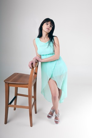 casually: girl standing beside chair casually leaning back Stock Photo