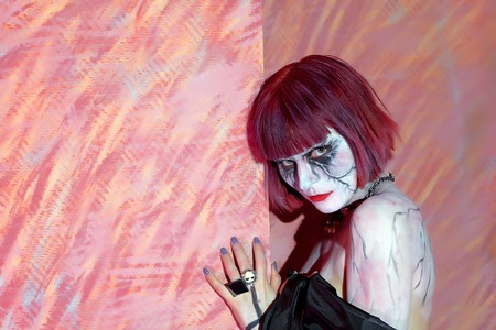 sinister: girl painted paints a sinister vampire on red background
