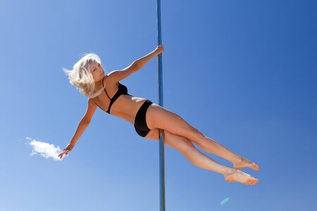 blonde in bathing suit on pole for dancing background of blue sky