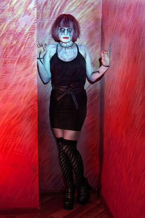 girl with makeup zombies standing in red wall opening