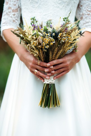 bride hand with bouquet of dried flowers and wheat ears in hands Stock Photo