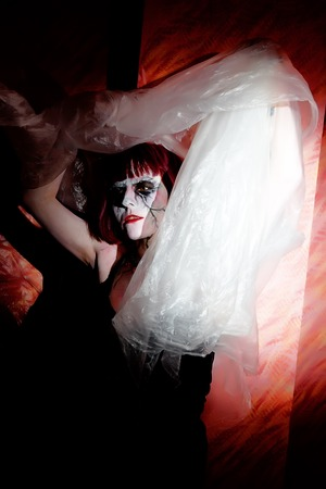 hellion: girl with makeup zombies waves mysterious veil on dark background
