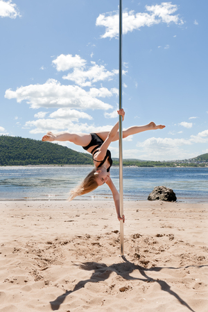 blonde dancing on pole for performing acrobatic summer beach