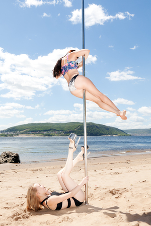 blond and brunette on pole for dancing on background of summer beach