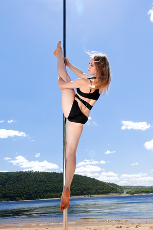 acrobatic performance girl in bathing suit on pole for dancing background of summer beach Stock Photo