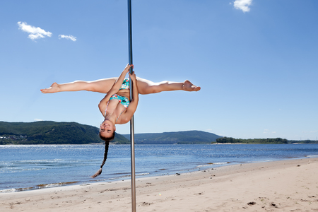 acrobatic performance laughing brunette woman in swimsuit on pole for dancing background of summer beach Stock Photo